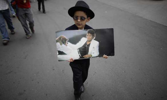 A Michael Jackson fan holds a picture of him during a daytime vigil in Mexico City, Saturday, June 27, 2009. Jackson died Thursday in Los Angeles at the age of 50. (AP Photo/Alexandre Meneghini)